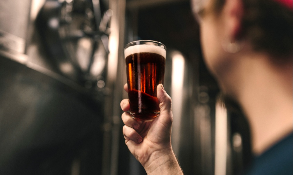 brewery holding up a beer